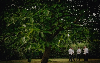 taking time with his groomsmen under a tree for a whiskey and cigar at doddington hall