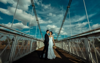 Bride and groom on Wilford Suspension Bridge with beautiful white fluffy clouds against a blue sky