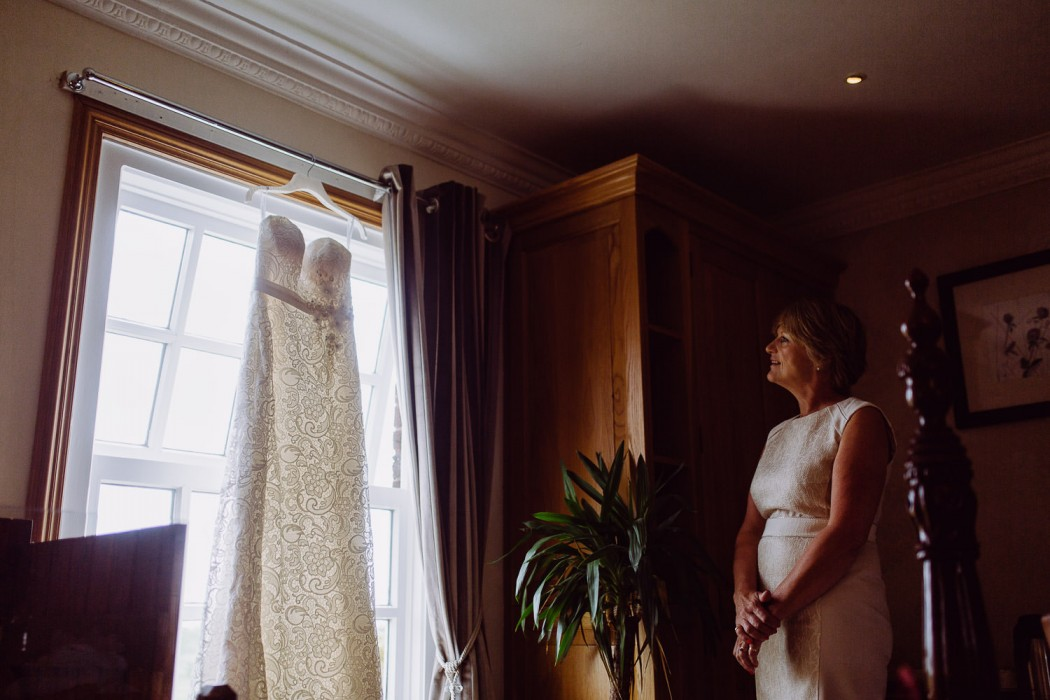 mum looks proudly at the wedding dress at swancar farm nottingham