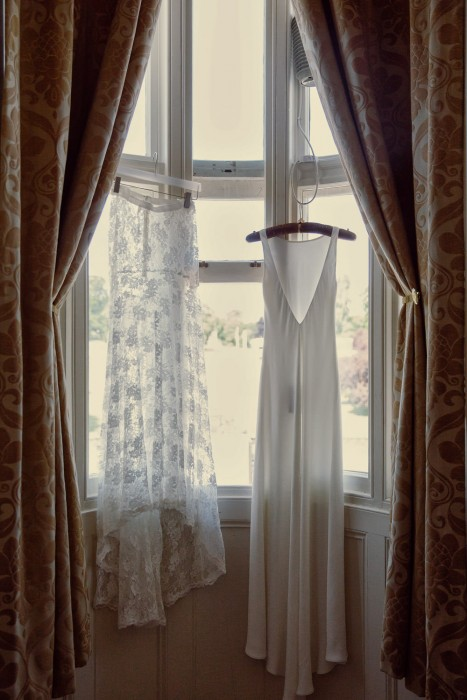 brides two piece dress hangs in the window at Stoke Rochford Hall