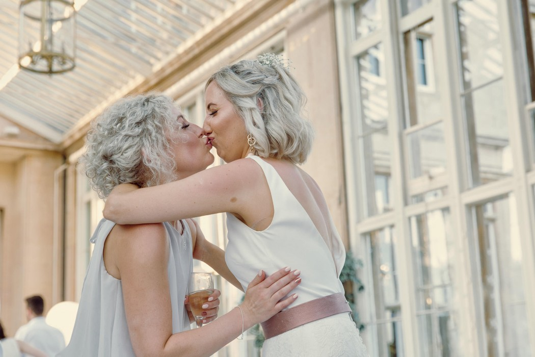 bridesmaid and bride have a kiss at the reception